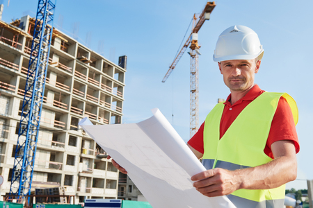 construction worker with blueprint at building area Stock Photo