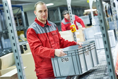 worker with box at warehouse conveyer Stock Photo