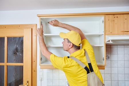 worker installing kitchen cupboard