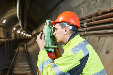 topografo: Surveyor with theodolite level at underground railway tunnel construction work Foto de archivo