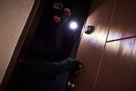 break-in of an apartment. Thief in mask with flashlight Stok Fotoğraf
