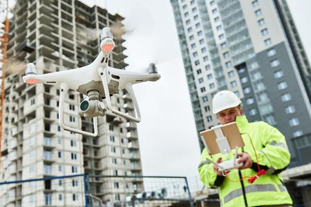 Dron obsługiwany przez pracownika budowlanego na placu budowy Zdjęcie Seryjne