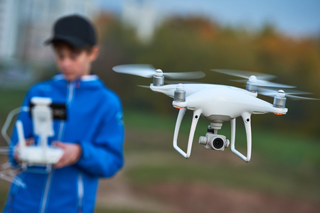 Young man operating of flying drone at sunset Stock Photo