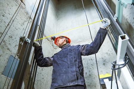 Maquinista con cinta métrica que controla la construcción del elevador en el pozo del ascensor Foto de archivo