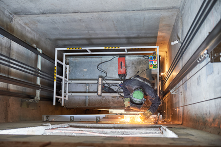 lift worker welding elevator fasteners in lift shaft Foto de archivo