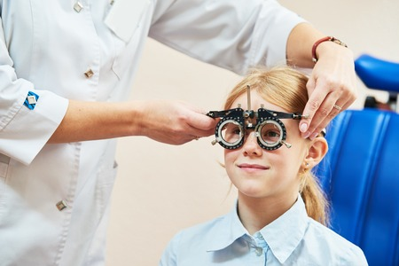 Child optometry concept. Young girl with phoropter during sight testing Archivio Fotografico
