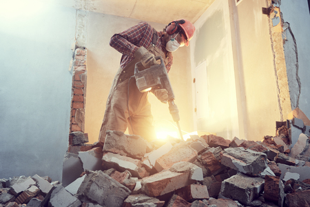builder with hammer breaking wall indoors 스톡 콘텐츠