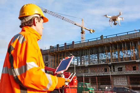 Dron obsługiwany przez pracownika budowlanego na placu budowy