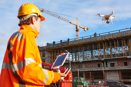 Drone operated by construction worker on building site Zdjęcie Seryjne - 92134511