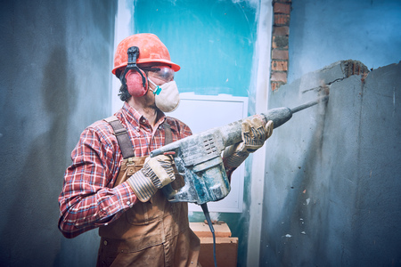 builder with hammer breaking wall indoors Stockfoto