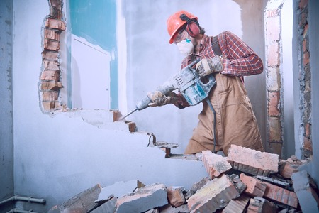 worker with demolition hammer breaking interior wall Фото со стока