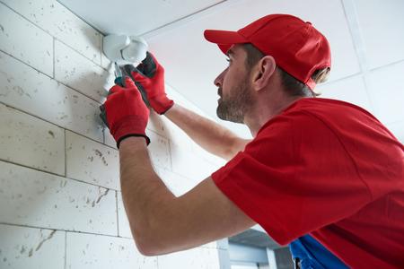 worker installing or adjusting motion sensor detector on the ceiling
