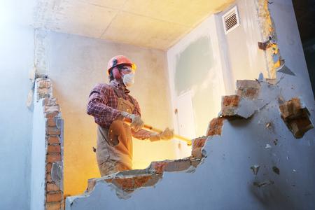 Trabalhador com marreta na parede interior destruindo Foto de archivo - 92406800