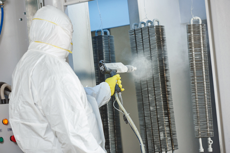 industrial metal coating. Man in protective suit, wearing a gas