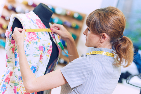 Female tailor works with jacket suit