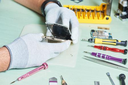 smart phone repair. repairman disassembling smartphone Standard-Bild