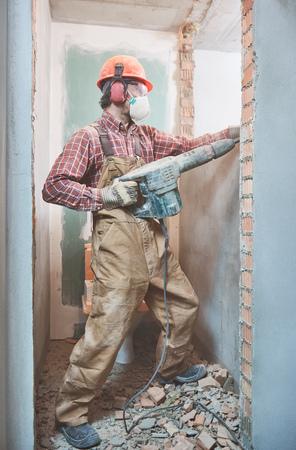 builder with demolition hammer breaking interior wall
