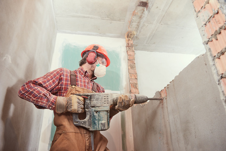 worker with demolition hammer breaking interior wall Banque d'images
