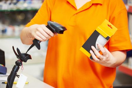Seller with barcode scanner in shop Standard-Bild
