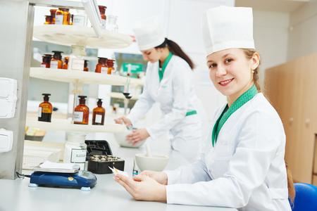 Female scientific pharmacy worker preparing medicine drug