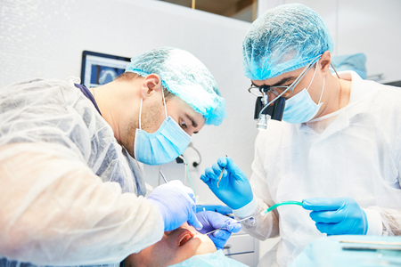 Two dentist perform dental operation on a patient