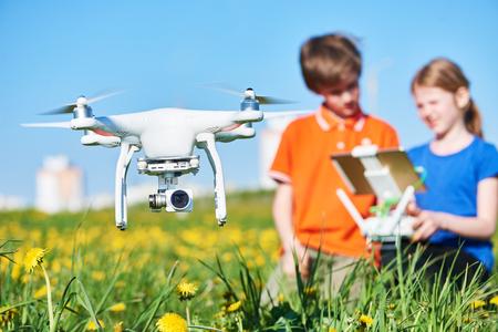 dzieci obsługujące latający dron o zachodzie słońca