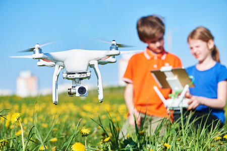 children operating of flying drone at sunset