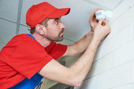 werknemer die de detector van de bewegingssensor op het plafond installeert of aanpast