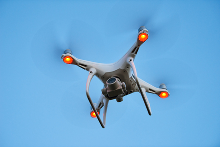 drone quadrocopter hovering in blue sky