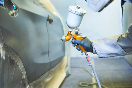 repairman painter in chamber painting automobile car bonnet Standard-Bild