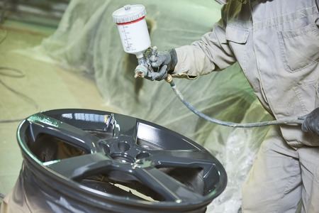 Automobile disc restoring. Painter painting light alloy wheel with spray Stockfoto