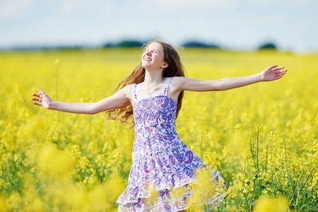 joyful girl with flower garland at yellow rape seed meadow Standard-Bild