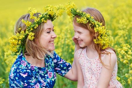 joyful woman little girl in flower garland at yellow field Standard-Bild
