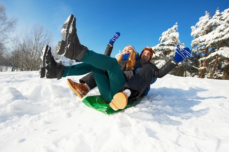 people in winter. young smiling couple sledding