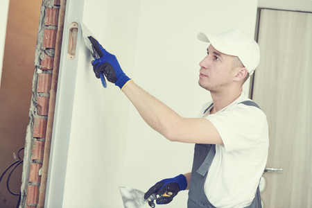 refurbishment. Worker spackling a wall with putty