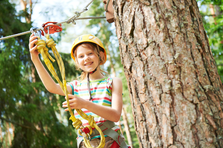 girl at climbing activity in high wire forest park Standard-Bild
