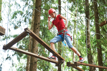 Girl at climbing activity in high wire forest park