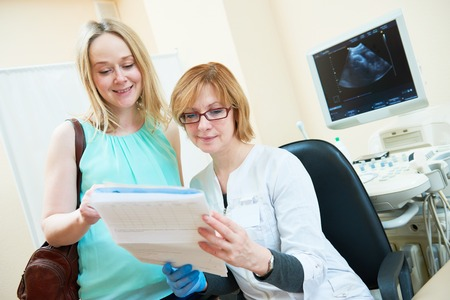 Ultrasound scan. Pregnancy. Gynecologist with patient and documents before test