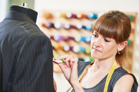 Female tailor works with male suit Standard-Bild
