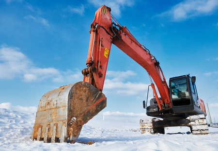 excavator loader machine at winter construction site