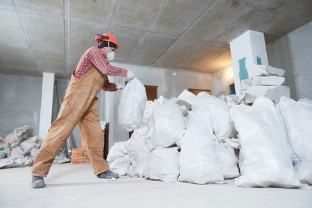 Worker collecting construction waste in bag Stockfoto