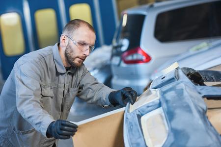 auto repairman worker with protecting paper in garage workshop Reklamní fotografie