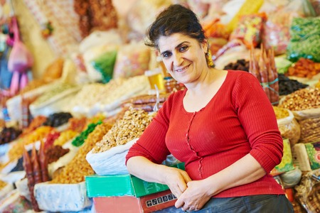 Portrait of senior woman near spice, nuts and other food on oriental market