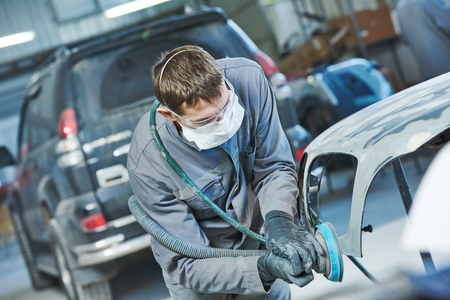 auto repairman grinding autobody bonnet Stock Photo