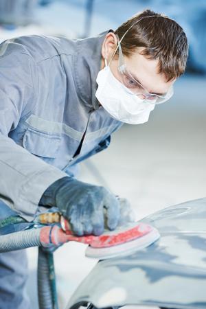 auto repairman grinding autobody bonnet Reklamní fotografie