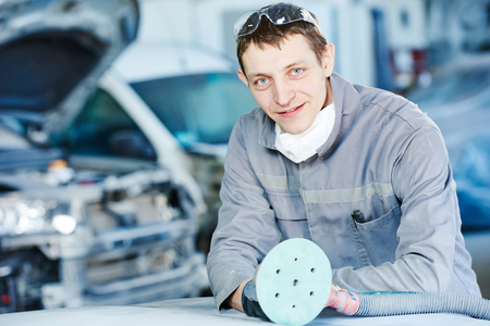 auto repairman with grinding machine