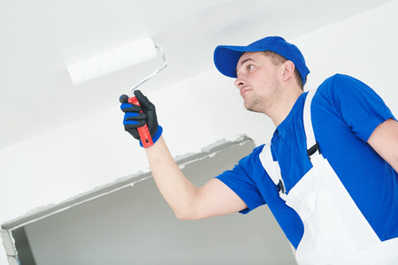 Painter painting ceiling with paint roller
