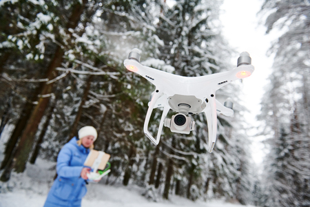 drone flying at winter snowy forest piloted by young woman Stock Photo