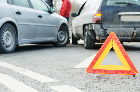 Accident or crash with two automobile. Road warning triangle sign in focus