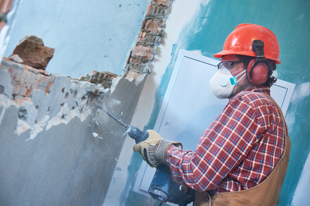 worker with demolition hammer breaking interior wall 스톡 콘텐츠